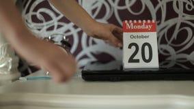 De kalender van de Desktop De vrouwen` s hand brengt een kalenderblad ten val stock footage