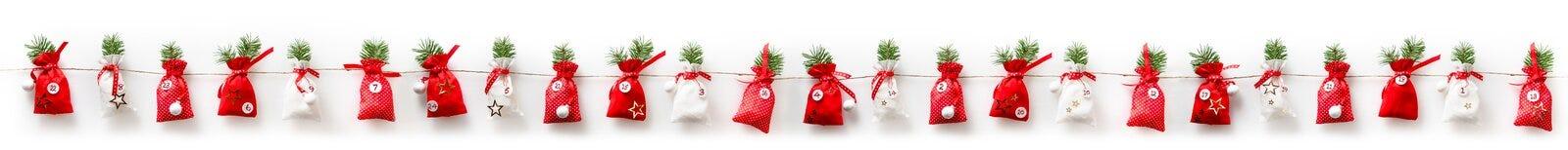 De kalender van de Kerstmiskomst vulde op een rij 24 sachets Stock Afbeelding
