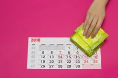 De kalender van menstruele vrouwen en een stapel gynaecologische stootkussens, vrouwelijke hand nemen een stootkussen, roze achte royalty-vrije stock foto