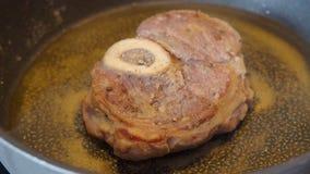 De kalfsvleesplak met mergpijp in bloem wordt gepaneerd is gebraden in een pan die