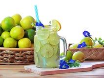 De kalk sneed vers citrusvruchtensap voor vers gedrukt die sap met ijs, met erwtenbloemen wordt verfraaid royalty-vrije stock afbeelding
