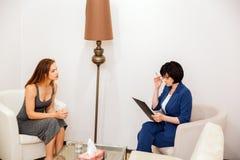 De kalme en vreedzame jonge vrouw zit voor psycholoog She zeer zorgvuldig luistert aan haar De arts is stock foto's
