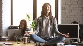 De kalme onderneemster zit op bureau mediteert beheert het werkspanning stock footage