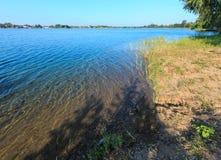De kalme rushy kust van het de zomermeer Stock Afbeelding