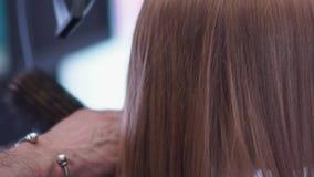De kam door het haar wordt gedragen, het haar is droog door hairdryer die Slow-motion stock footage