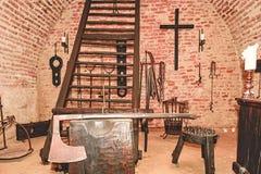 De kamer van de inquisitiemarteling Oude middeleeuwse martelingskamer met vele pijnhulpmiddelen Stock Fotografie