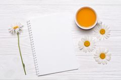 De kamille bloeit, notitieboekje met plaats voor tekst, kop met thee op wit Royalty-vrije Stock Afbeeldingen