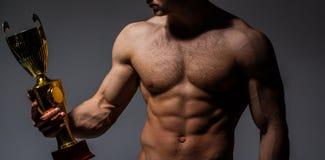 De kampioens` s kop, mens ` s houdt gouden kop Winnaar sterke mens, sport, professionele kampioen Spiermens, naakt mannetje stock foto