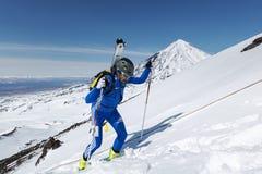 De Kampioenschappen van het skialpinisme: de skibergbeklimmer beklimt aan berg met skis aan rugzak worden vastgebonden die Stock Foto