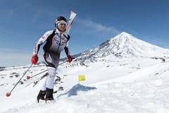 De Kampioenschappen van het skialpinisme: de skibergbeklimmer beklimt aan berg met skis aan rugzak worden vastgebonden die Royalty-vrije Stock Foto