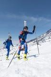 De Kampioenschappen van het skialpinisme: de twee die skibergbeklimmer beklimt aan berg met skis aan rugzak worden vastgebonden Royalty-vrije Stock Afbeelding