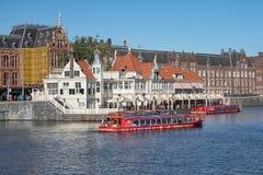 De kanalen van Amsterdam met lanceringen en gebouwen dichtbij centraal station stock afbeeldingen