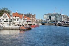 De kanalen van Amsterdam met lanceringen en gebouwen dichtbij centraal station royalty-vrije stock afbeelding