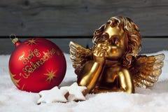 De kaneel van Kerstmisbollen speelt gouden putto op stapel van sneeuw mee Stock Afbeelding