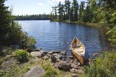 De kano van een visser op rotsachtige kust in het noordelijke meer van Minnesota stock foto's