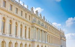 De kant van het paleis met standbeelden op bovenkant in Versailles Stock Foto