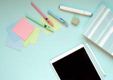 De kantoorbehoeften op een blauwe achtergrond stock fotografie