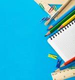 De kantoorbehoeften van de school op het blauw Royalty-vrije Stock Afbeeldingen