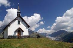 De kapel van de berg met gletsjer Aletsch Stock Foto's