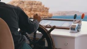 De kapitein controleert het toeristenjacht in overzees onweer dichtbij de rotsen Stuurwiel van een plezierboot stock footage