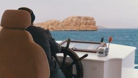 De kapitein controleert het toeristenjacht in overzees onweer Stuurwiel van een plezierboot stock videobeelden
