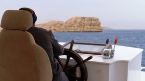 De kapitein controleert het toeristenjacht in overzees onweer Stuurwiel van een plezierboot stock footage