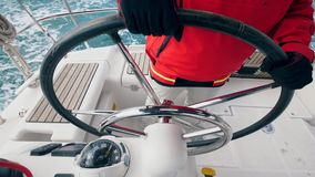 De kapitein houdt een stuurwiel van een boot stock videobeelden