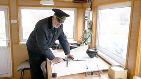 De kapitein van het schip brengt de navigatieroute op de kaart in de stuurhut in kaart stock videobeelden