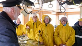 De kapitein van het schip van Noorwegen in de stuurhut neemt instructies voor zijn team stock video