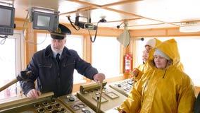 De kapitein van het schip van Noorwegen in de stuurhut spreekt met zijn team en geeft hen instructies stock video
