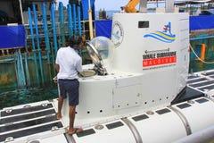 De kapitein van de toeristen witte onderzee?r in de haven van Mannetje maakt een laatste inspectie v??r de onderdompeling stock foto