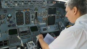 De kapitein van vliegtuig bereidt documenten vóór vluchtzitting in voor cockpit stock video