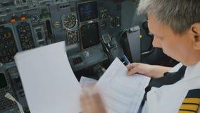 De kapitein van vliegtuig controleert documenten vóór vlucht stock footage
