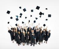 De Kappen van de graduatie die in de Lucht worden geworpen Stock Foto