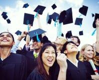 De Kappen van de graduatie die in de Lucht worden geworpen royalty-vrije stock foto's