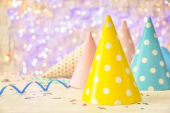 De kappen van de verjaardagspartij op lijst tegen lichten stock foto