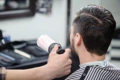 De kapper bestrooit een cliënt met borstel royalty-vrije stock afbeeldingen