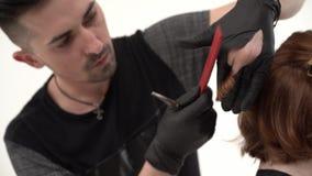De kapper die een kapsel voor zijn cliënt met gemberhaar uitvoeren, het holsing kamt en schaar stock video