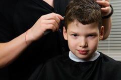 De kapper doet een kapsel voor de jongen stock fotografie