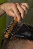 De kapper doet haar met borstel en hairdryer van cliënt in professionele herenkapper royalty-vrije stock fotografie