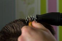 De kapper doet haar met borstel en hairdryer van cliënt in professionele herenkapper stock afbeelding