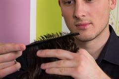 De kapper doet haar met borstel van cliënt in professionele herenkapper stock afbeelding