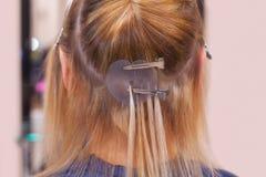 De kapper doet haaruitbreidingen aan een jong meisje, een blonde in een schoonheidssalon stock foto