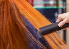 De kapper doet haaruitbreidingen aan een jong meisje, een roodharigemeisje in een schoonheidssalon royalty-vrije stock foto's