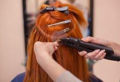 De kapper doet haaruitbreidingen aan een jong, roodharig meisje royalty-vrije stock afbeeldingen