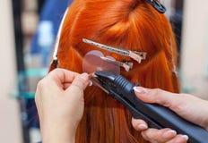 De kapper doet haaruitbreidingen aan een jong, roodharig meisje, in een schoonheidssalon stock fotografie
