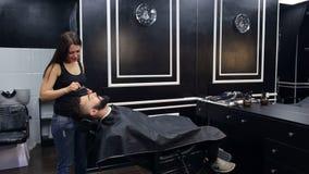 De kapper doet het stileren van een baard aan een mens stock footage
