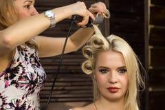 De kapper doet kapsel voor luxueuze blonde vrouw kapsel in de vorm van grote krul Het kapsel van het conceptenhuwelijk royalty-vrije stock foto