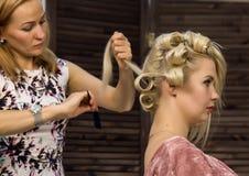 De kapper doet kapsel voor luxueuze blonde vrouw kapsel in de vorm van grote krul Het kapsel van het conceptenhuwelijk stock fotografie