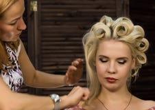 De kapper doet kapsel voor luxueuze blonde vrouw kapsel in de vorm van grote krul Het kapsel van het conceptenhuwelijk stock foto